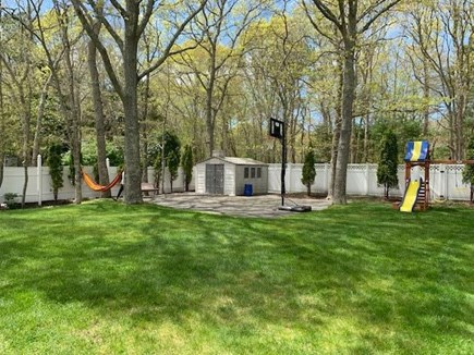 Mashpee, Popponesett Beach Cape Cod vacation rental - Back Yard view of Basketball court & Swing Set.  Totally fenced
