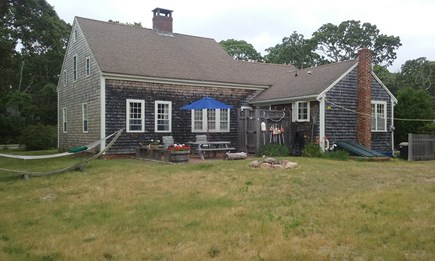 North Eastham Cape Cod vacation rental - Rear of house w/outdoor shower - brick patio w/picnic table.