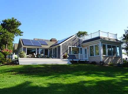 East Orleans Cape Cod vacation rental - View of back deck -- and solar panels -- from bay side of home
