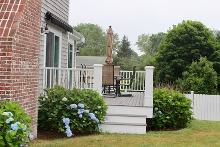 West Yarmouth Cape Cod vacation rental - Side yard deck with table and chairs and awning