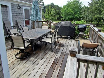 Eastham Cape Cod vacation rental - Back deck with barbeque, lounge chairs, and large patio table.