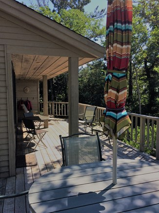 Wellfleet Cape Cod vacation rental - A view of the deck with dining table, waterfront is to the right