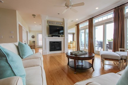 Barnstable Cape Cod vacation rental - Living room with gas gireplace & 3 sliders to deck