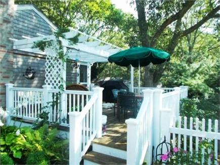 Dennis Cape Cod vacation rental - Side deck off kitchen. Table for 8, grill, extra seating.