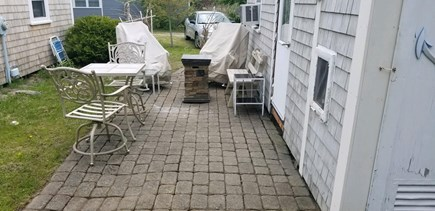 Eastham Cape Cod vacation rental - Side entrance and patio with grill, firepit, and seating