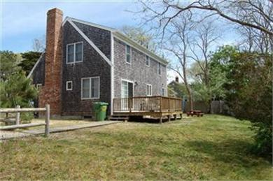 North Eastham Cape Cod vacation rental - Back yard & deck, plenty of driveway parking behind split rail