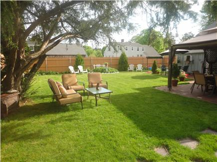 Hyannis Cape Cod vacation rental - fenced in yard with beautiful landscaping and gazebo canopy