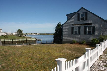 West Dennis Cape Cod vacation rental - House - Side Yard View - Fenced yard along the water