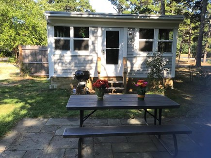 Eastham Cape Cod vacation rental - Relax on back patio with many birds & trees , grill available.