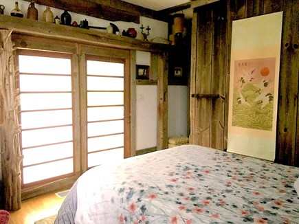 No. Truro Cape Cod vacation rental - Bedroom with queen size bed and open glass door from porch