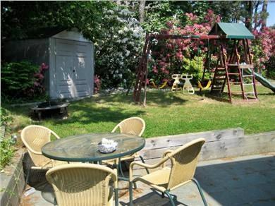 Mashpee, Popponesset Cape Cod vacation rental - Back yard: slate patio + playset for small children