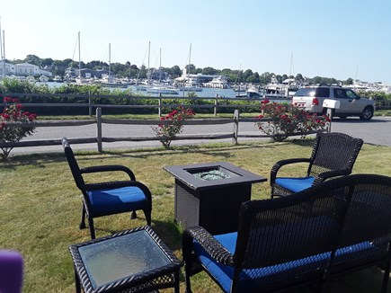 On Falmouth Harbor, Desirable  Cape Cod vacation rental - Fire Pit and iron umbrella table for dining with harbor views.
