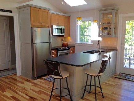 South Orleans Cape Cod vacation rental - Kitchen with Breakfast Bar and Dining Area Open to Deck