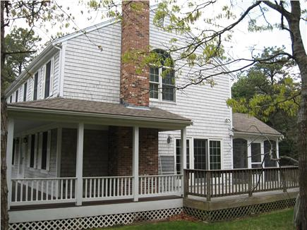 Dennis Cape Cod vacation rental - Right side of house with bbq/ two loungers with table( in season)