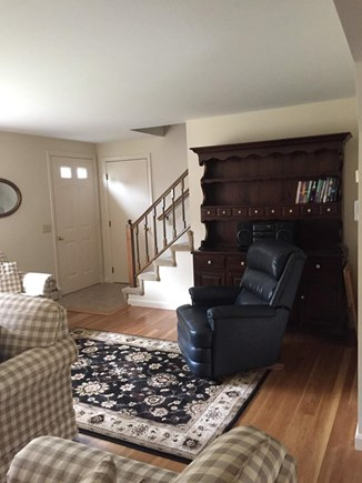 South Dennis Cape Cod vacation rental - Living room, front door, and the stairs to second floor.