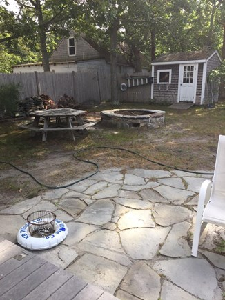 West Harwich Cape Cod vacation rental - large backyard with a patio and fire pit