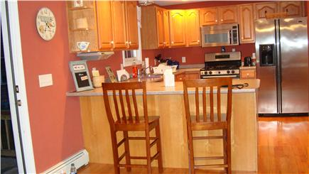 East Falmouth Cape Cod vacation rental - Kitchen with breakfast bar and sliders to back deck.