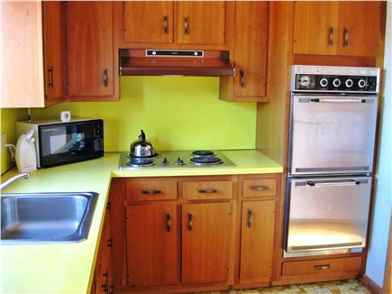 East Sandwich Cape Cod vacation rental - Kitchen with frig. opposite the oven. Pots, pans & utensils.