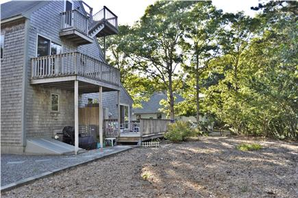 Mashpee Cape Cod vacation rental - View of back yard & second deck; garage and grill area to left