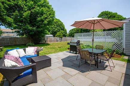 West Yarmouth Cape Cod vacation rental - Backyard dining, patio set w/ umbrella, fire pit and BBQ