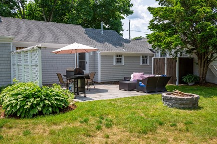West Yarmouth Cape Cod vacation rental - Backyard dining, patio set w/ umbrella, picnic table & fire pit
