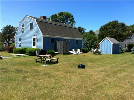 North Eastham Cape Cod vacation rental - Back yard with gas grill. seating. umbrella, fire pit and shed