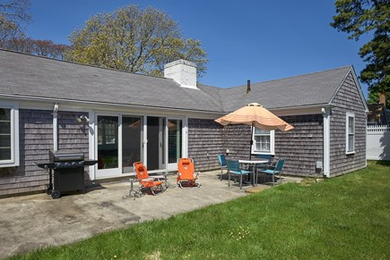 West Harwich Cape Cod vacation rental - Backyard patio, gas grill, plenty of seating, full green lawn.