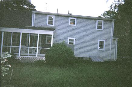 East Dennis Cape Cod vacation rental - Screened porch w/ white wicker furniture, level yard for games