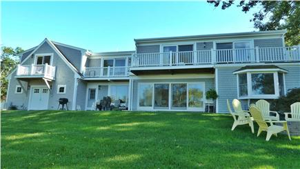 Brewster Cape Cod vacation rental - Back of house with the fire pit, gas grill, and patio.
