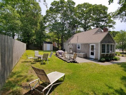 Dennis Cape Cod vacation rental - Backyard with view of patio and firepit.