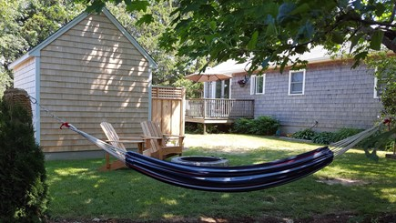Sandwich Cape Cod vacation rental - Back yard with large outdoor shower, fireplace and hammock.