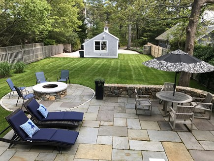 Seconsett Island, Mashpee Cape Cod vacation rental - Bluestone Patio with table, loungers, stonewall and fire pit