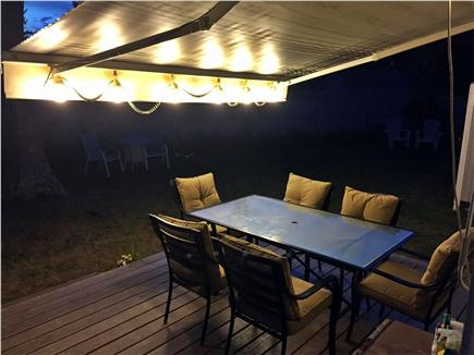 Dennis Port Cape Cod vacation rental - Backyard at night with awning and lights
