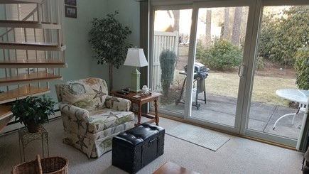 Brewster Cape Cod vacation rental - View of living room from dining room, sliders lead to patio.