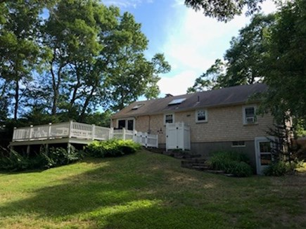 Dennis Cape Cod vacation rental - Back of house with a fenced in yard for playtime with the kids.