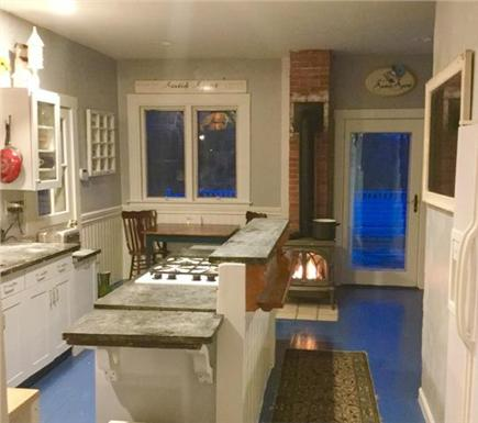 Barnstable Cape Cod vacation rental - Kitchen with wood burning fireplace on and back door to deck.