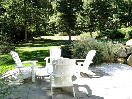 Barnstable Cape Cod vacation rental - Adirondack chairs on patio, overlooking large back yard