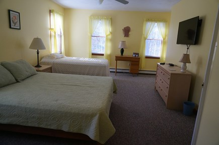 Eastham Cape Cod vacation rental - Bedroom with one queen and one twin bed and a wall mounted tv.