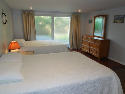 Chatham Cape Cod vacation rental - Downstairs bedroom w/ two queen beds, slider to back yard, and TV