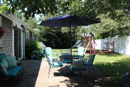 West Harwich Cape Cod vacation rental - Large backyard with swing set and multiple seating areas