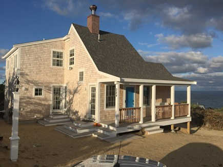 Wellfleet Cape Cod vacation rental - Driveway view of cottage, ocean in the background.