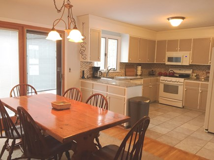 Harwich Cape Cod vacation rental - Dining / Kitchen with Door out to large deck and fire pit area