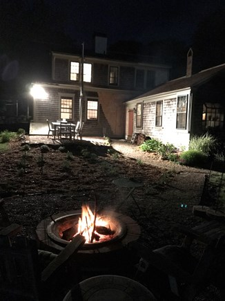 Harwich Cape Cod vacation rental - Firepit at night with view toward back of the house.