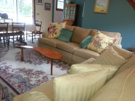 Wellfleet Cape Cod vacation rental - Living Room in foreground and Dining Room w/slider to the deck