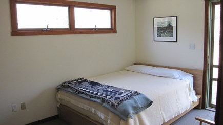 Truro Cape Cod vacation rental - Main level bedroom with queen bed opens to the wooded yard