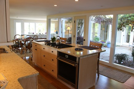 Chatham Cape Cod vacation rental - Jenn-Air kitchen with 36 in. cooktop in island with Atrium behind