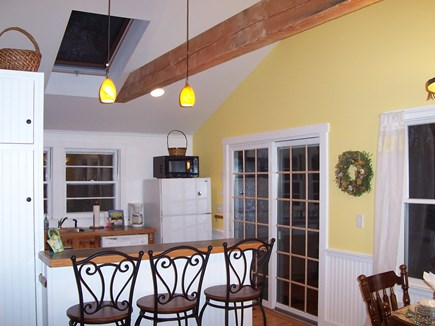 Eastham Cape Cod vacation rental - Kitchen island & stools, beams and skylight. Doors lead to deck.