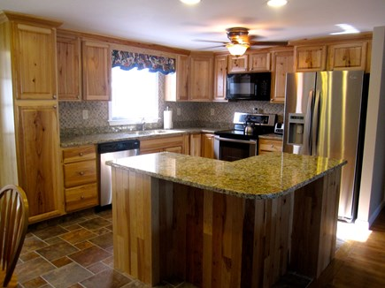 West Dennis Cape Cod vacation rental - Kitchen has granite counters with island and hickory cabinets.