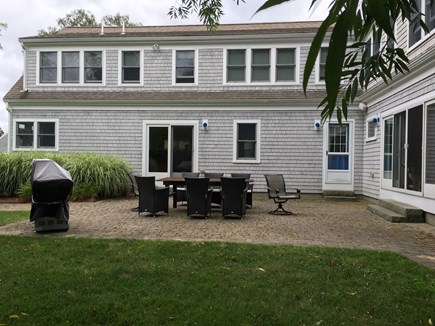 Dennis Cape Cod vacation rental - Backyard patio, outside table and chairs and gas grill.