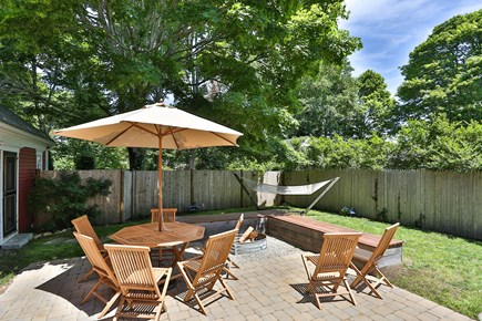 Harwich Center Cape Cod vacation rental - Back yard dining area with fire pit, bench seating + big hammock